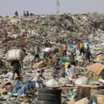FILE PHOTO: In this photo taken Friday, Jan, 24. 2014, scavengers in Lagos, Nigeria sort out iron and plastic to sell at the Olusosun dump site the city's largest dump. With a population of more than 20 million, garbage piles up on streets, outside homes and along the waterways and lagoons, creating eyesores and putrid smells. The booming city also has major electricity shortages and many residents rely on diesel generators that cloud the air with black exhaust.  Nigeria's most populous city is turning these problems into an advantage by starting a program to convert waste into methane gas to generate electricity. A pilot program at a local market has already shown success on a smaller scale. Lagos' waste management program is also organizing recycling to clean up the country's biggest city.  (AP Photo/ Sunday Alamba)