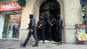 Spanish police stand guard outside an apartment building during a sweeping operation at some 12 locations [Photo Credit: The Express Tribune]
