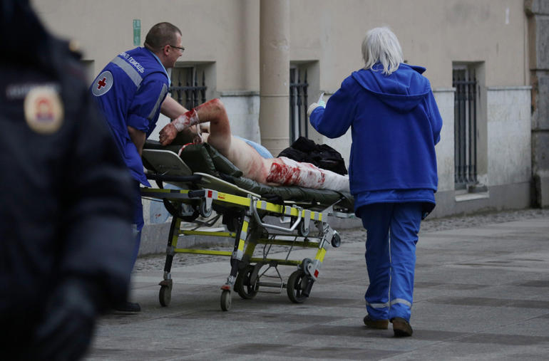 REFILE - EDITORS NOTEAn injured person is helped by emergency services outside Sennaya Ploshchad metro station, following explosions in two train carriages at metro stations in St. Petersburg, Russia April 3, 2017. REUTERS/Anton Vaganov  ATTENTION EDITORS - VISUAL COVERAGE OF SCENES OF INJURY OR DEATH