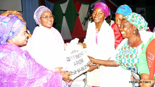 Wife of the President, Aisha Buhari presenting food items to some women