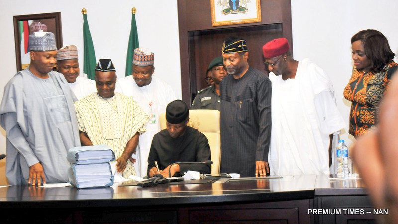 Acting President Yemi Osinbajo signing the 2017 Appropriation Act into law at the Presidential Villa in Abuja on Monday (12/6/17). With him from left are: Senate President Bukola Saraki; Speaker, House of Representatives, Yakubu Dogara; Senior Special Assistant to the President on National Assembly Matters (Senate), Sen. Ita Enang; Senior Special Assistant to the President on National Assembly Matters (House of Representatives), Suleiman Kawu; Minister of Budget and National Planning, Sen. Udoma Udo Udoma; Chief of Staff, Alhaji Abba Kyari; and Minister of Finance, Mrs Kemi Adeosun.  03181/ 12/6/2017/Callistus Ewelike/BJO/NAN