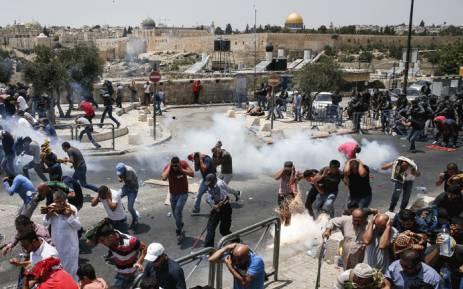 Palestinian worshippers run for cover from teargas fired by Israeli forces outside Jerusalem's Old City in front of the Al-Aqsa mosque compound on 21 July 2017. [Photo Credit: ewn.co.za]