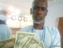 Photos of Garba Bakono, a pilgrim from Nasarawa State, displaying two $2 US and four $1 US denominations and envelope handed to him, that was supposed to contain $800.