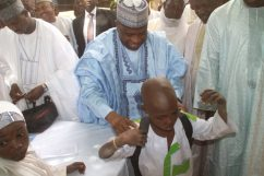 Governor Aminu Waziri Tambuwal presenting a school bag to young Safiyanu Adamu after he was enrolled in school for the first time, at the flag-off of Sokoto state school enrollment drive in Riji, Rabah LGA.