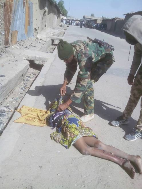 A soldier defusing a bomb best from the body of a shot suicide bomber.