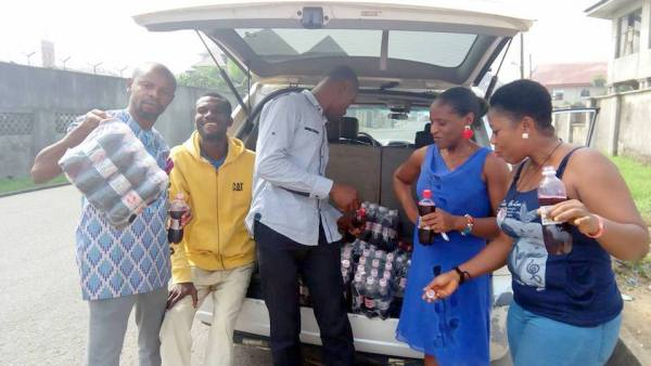 Mr. Collins Oscar (2nd from left) selling zobo on the street