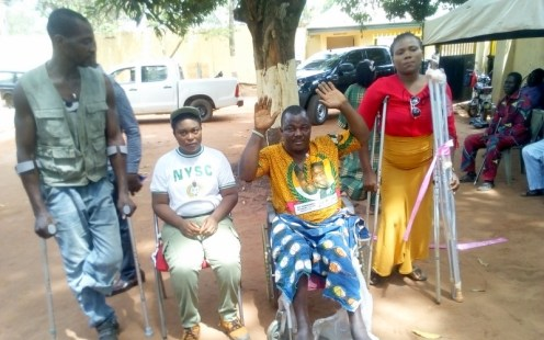 Miss Jennifer Ejiogu with the Physically challenged persons who are beneficiaries of Aids she donated at Rehabilitation Centre at Oba Anambra State