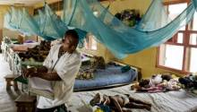 A health worker attending to sick patients in a hospital ward