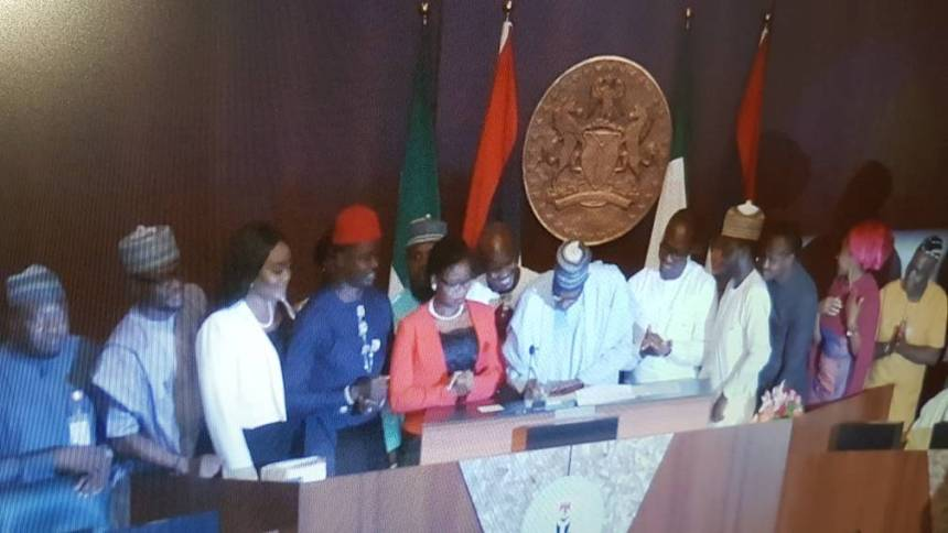 "President Muhammadu Buhari signing the ""Not to young to Run"" bill."