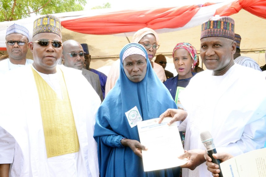 Borno State Governor, Kashim Shettima, one of the Boko Haram Victim A Widow Beneficiaries receiving the letter from Chairman and Founder Aliko Dangote Foundation, Aliko Dangote