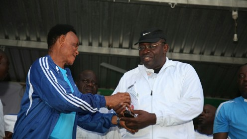 Former Coach of the Super Eagles of Nigeria, Monday Sinclair (left) on behalf of the Local Organising Committee of the 2nd Governor Henry Seriake Dickson Football Tournament, presenting a souvenir to the Governor of Bayelsa State, Hon. Seriake Dickson (right) for his love/ promotion of Sports in the State during the closing ceremony/finals of the competition at the Samson Siasia Sports Complex in Yenagoa, while the State Commissioner for Sport, Hon. Perekiye Buruboyefe (centre) looks on. Photo by Lucky Francis