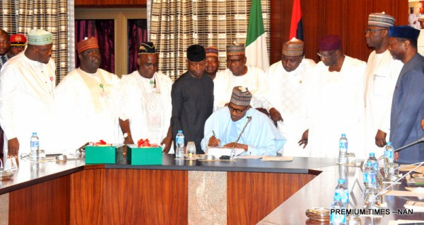 President Muhammadu Buhari signing the 2018 Appropriation Bill into law at the Presidential Villa in Abuja on Wednesday (20/6/18). Standing with him are: Senior Special Assistant to the President on National Assembly Matter (House) Suleiman Kawu; Representative of the Senate President, Sen Ibn Na'ala; Senior Special Assistant to the President on National Assembly Matter (Senate) Sen Ita Enang; Vice President Yemi Osinbajo; Chairman, Senate Committee on Appropriation, Sen Danjuma Goje; Representative of Speaker, House of Representatives, Rep Ado Doguwa; Chief of Staff, Alhaji Abba Kyari; Secretary to the Government of the Federation, Mr Boss Mustapha and Minister of Budget and National Planning, Sen Udoma Udo Udoma. 03268/20/6/2018/Callistus Ewelike/NAN