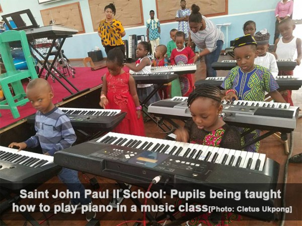 Saint John Paul II School - Pupils being taught how to play piano in a music class