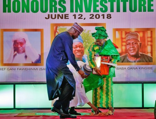 President Buhari bends down to assist Mrs Ganiyat Fawehinmi with an item that fell off her during the Special National Honours Investiture in celebration of June 12. [Photo: @bayoomoboriowo]