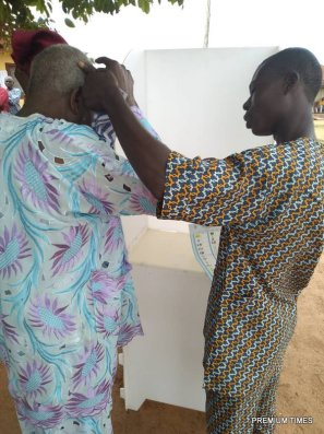 11:30 am, Odeyemi Ege, a blind man being assisted by his son to be verified and vote at Unit 9, ward 7. His son asked him who he wanted to vote, he said so and his son obliged to the admiration of police officers on ground. There are 412 registered voters expected to vote here. According to Famodun Omolola the PO, Voting started by 8:am. As at the time of this report, there was still much people lined up to vote.