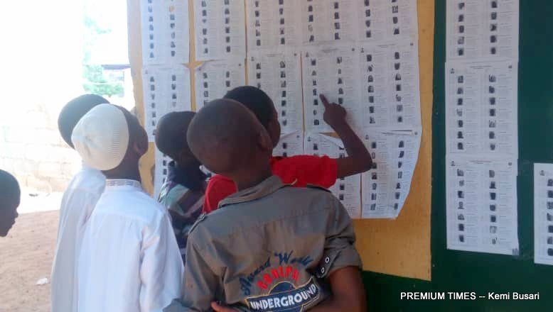Children checking pictures of acquaintances on voters' register