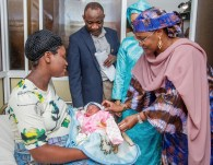 Mrs. Buhari admiring another baby, with her Mrs. Barrow and the Medical Director of the Hospital