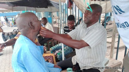 Amzat shaving a customer