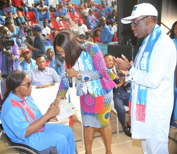 Delta State Governor, Senator Ifeanyi Okowa (right), watching as his wife Dame Edith presents certificate and Cheque to a Gold medalist, Evelyn Paragon at the Reception/Award of Athletes and Officials to the 4th National Youth Games 2018 and the 19th National Sports Festival, Abuja, in Asaba. PIX: BRIPIN ENARUSAI