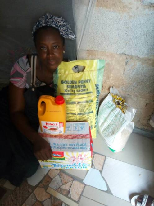 One of the widows of the victims of the insurgency in the northeast with some of the food items presented to her by the Glorious Vessels Foundation during an outreach in Abuja recently