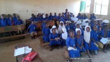 Students in a packed classroom without desks and chairs