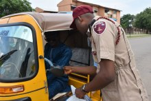 FRSC Corps Marshal verifying a tricycle License