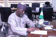Mohammed Sambo submitting and signing his letter of appointment at the NHIS head office in Abuja on Tuesday.