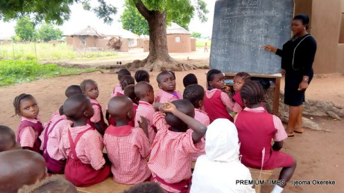Children in a school receiving classes under a tree (out-of-school children)