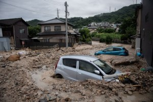 """A picture shows cars trapped in the mud after floods in Saka, Hiroshima prefecture on July 8, 2018. – Japan's Prime Minister Shinzo Abe warned on July 8 of a """"race against time"""" to rescue flood victims as authorities issued new alerts over record rains that have killed at least 48 people. (Photo by Martin BUREAU/AFP)."""