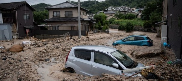 "A picture shows cars trapped in the mud after floods in Saka, Hiroshima prefecture on July 8, 2018. – Japan's Prime Minister Shinzo Abe warned on July 8 of a ""race against time"" to rescue flood victims as authorities issued new alerts over record rains that have killed at least 48 people. (Photo by Martin BUREAU/AFP)."