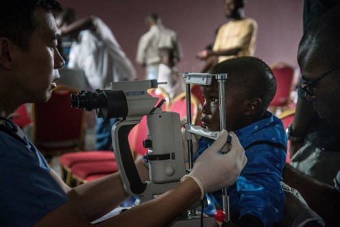 Muhindo, a young Ebola survivor, has his eyes tested by Dr Steven Yeh. (Credit: WHO/J.D. Kannah)