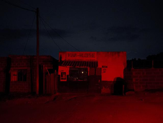 A store with a candle burning in the window is lit by the brake lights of a parked car during load shedding in Embo, South Africa