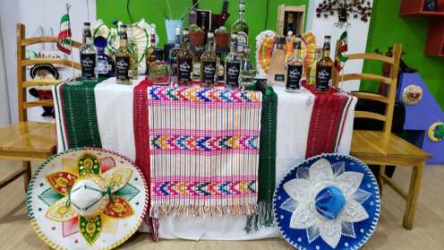 Bottles of Tequila at the event, ringed by Mexican hats and cotton cloth .
