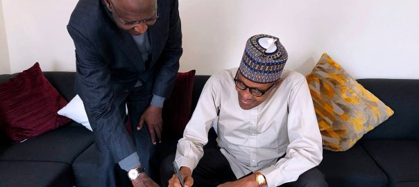 Buhari signing the amended Bill into law [PHOTO CREDIT: @MBuhari]