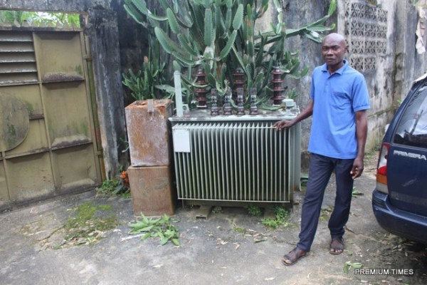 Ikot Ekan's village assistant youth secretary, Ime Equere, standing beside the transformer in the house of the head of the village council.