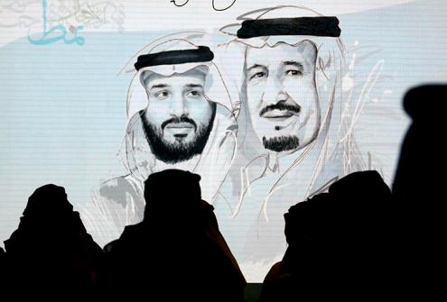 "FILE- In this Monday, Oct. 28, 2019, file photo, Saudi participants at the Future Investment Initiative, ""FII"" stand for the national anthem in front of a screen displaying images of Saudi King Salman, right, and Crown Prince Mohammed bin Salman, a day before it will be held in Riyadh, Saudi Arabia. Saudi Arabia has detained at least eight intellectuals and former bloggers in a fresh wave of arrests targeting people with links to reformers. (AP Photo/Amr Nabil)"