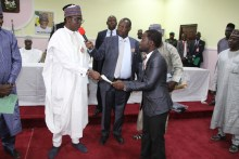 Gov. Buni presenting cheque and laptop to a male beneficiary at the event.