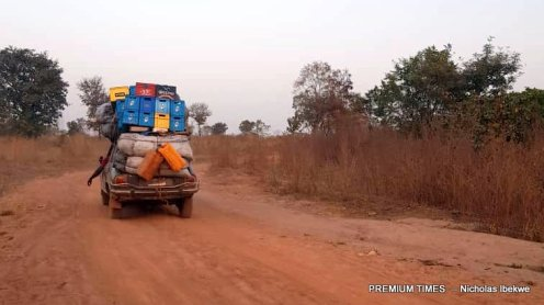 A vehicle laden with goods on the bumpy Okerete border road.
