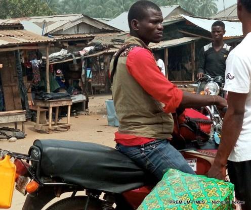 Okada riders and petty smugglers haggling over price of petrol in kegs