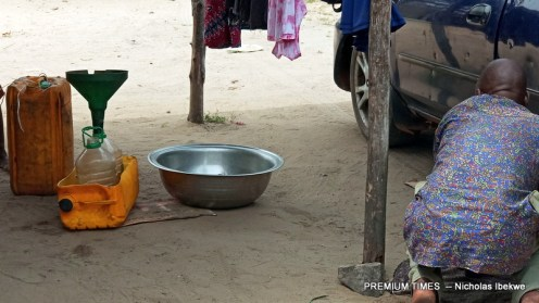 A man drawing fuel from the tank of his car into keg at Owode- Apa