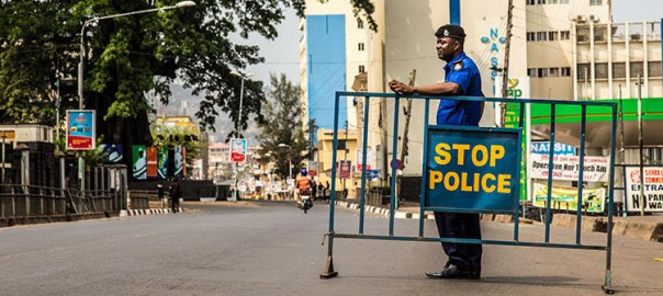 A Sierra Leone Policeman guards a road block forming part of a three day country wide lockdown on movement of people due to the Ebola virus in the city of Freetown, Sierra Leone, Friday, March. 27, 2015. Sierra Leone's 6 million people were told to stay home for three days, except for religious services, beginning Friday as the West African nation attempted a final push to rid itself of Ebola. (AP Photo/ Michael Duff)