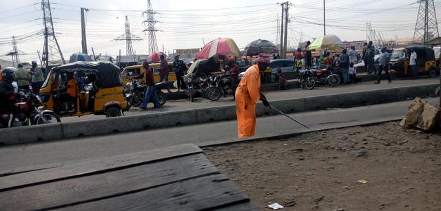 Kehinde Raji sweeping the street at Suru, Lagos