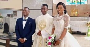 The couple pose with the officiating priest