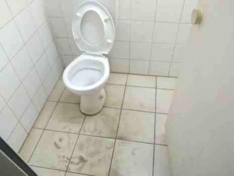 A toilet in the admin bloc at the National Hospital Abuja. Water splashed all over the floor. No tissues or cleaning products.