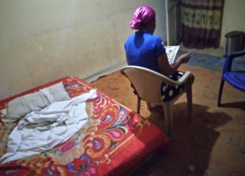 Emilia sitting in her one room apartment at Ojo barracks