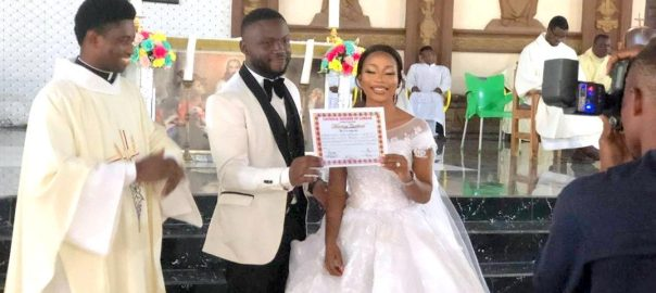 A newly wedded couple displaying their marriage certificate