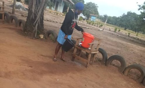 Sagamu high school student putting water inside basin PHOTO CREDITS: Premium Times - Alfred Olufemi