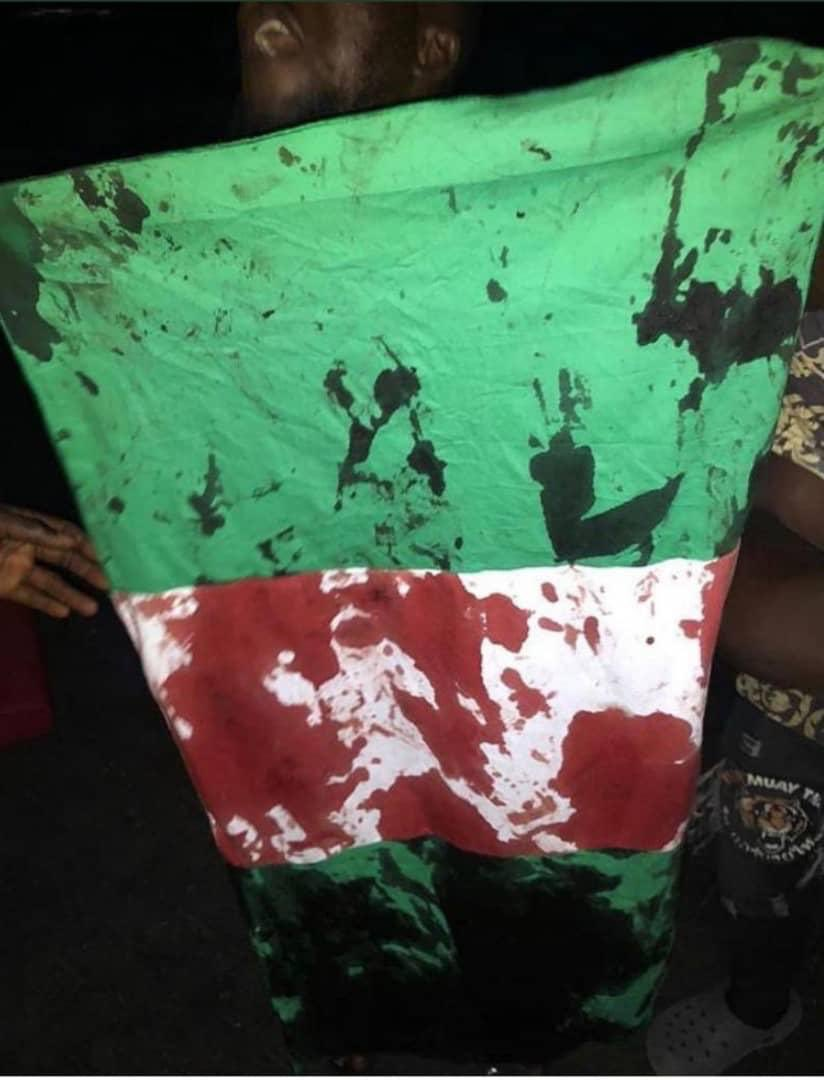 #EndSars: Blood stains on the Nigerian flag. After security operatives opened fire on peaceful protesters at Lekki toll gate, Lagos. [Source: Twitter]