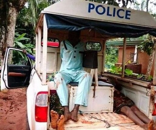 The suspect being taken to the police station alongside remains of his parents in a police van