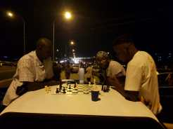 People stuck in the mammoth traffic jam enjoy a game of chess to pass the time.
